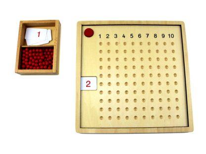 Cuenta con un tablero de madera con números del 1 al 10 a lo largo de la parte superior y con orificios para colocar las perlas. Incluye tarjetas del 1 al 10 que representan el multiplicando.