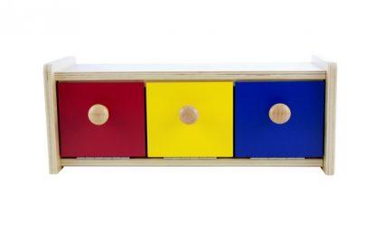 La caja con cajones de colores desarrolla la coordinación ojo-mano e indirectamente permite que el niño experimente la permanencia del objeto.