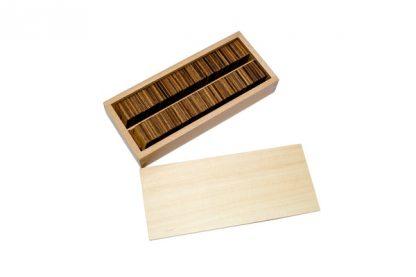 Este material consiste en un tablero de madera cuadiculado de color rojo con números del 1 al 10 tanto en vertical como en horizontal