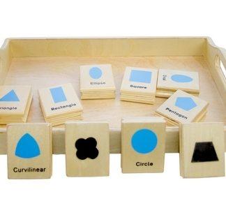 Este material Montessori consiste en una caja de madera que contiene 10 piezas de madera con dibujos de figuras geómetricas por un lado y por el otro lado es un sello de la misma figura,vista frontal,foto redes sociales,mmm399
